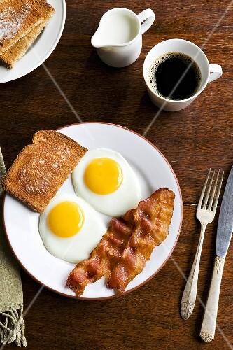 Frühstück mit Spiegelei, Bacon, Toast und Kaffee