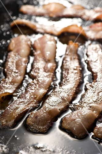 Thick Slices of Hickory Smoked Bacon Frying on Griddle