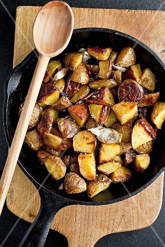 Cinnamon Roasted Potatoes in a Cast Iron Skillet; With Wooden Spoon; From Above