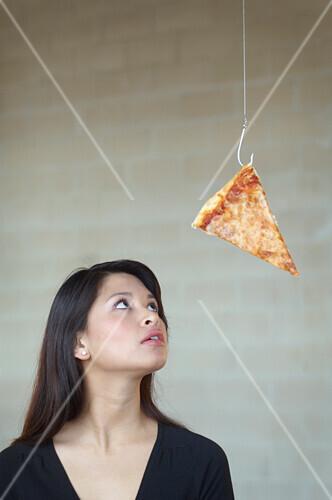 Asian woman looking at pizza on hook, Richmond, VA
