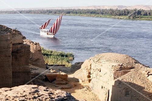 Blick über Steinruinen auf Boot mit rotweissen Segeln auf dem Fluss, Nil, Ägypten
