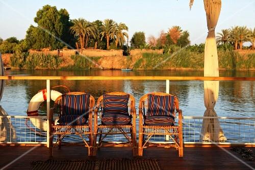 Abendstimmung auf Bootsdeck mit Korbstühlen vor der Reling und Dschungelblick, Nil, Ägypten