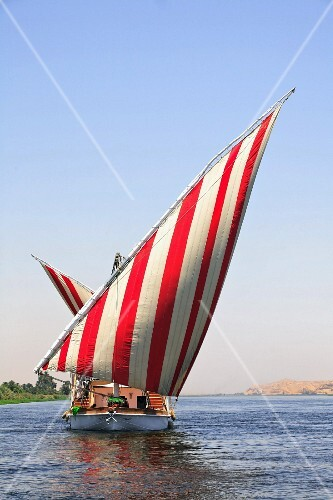 Segelboot mit rotweiss gestreiften Segeln auf dem Fluss, Nil, Ägypten