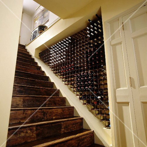 A flight of old wooden stairs and a wine storage area in a niche
