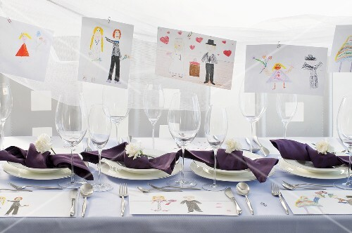 A festively laid table with children's drawings hanging in the background