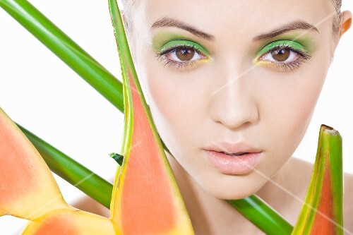 A young woman with green make-up and a plant
