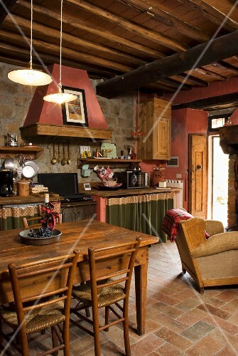 An open-plan living room with a dining area and a kitchen in a rustic Mediterranean county-house