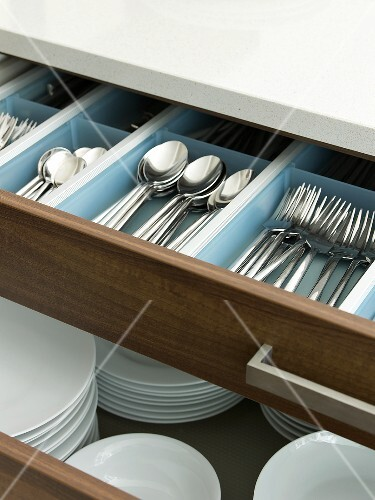 Open drawers containing cutlery and plates
