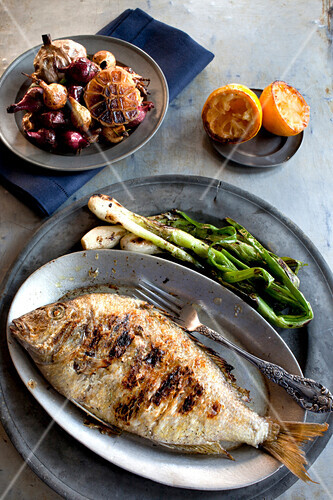 Plates of grilled fish, vegetables and garlic